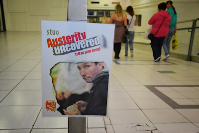 26-06-2013 - By Scott Campbell (+44) 0774 296 870 - 'Austerity Uncovered', in Cumbernauld Town Centre; Picture shows Austerity Uncovered poster with background crowd.