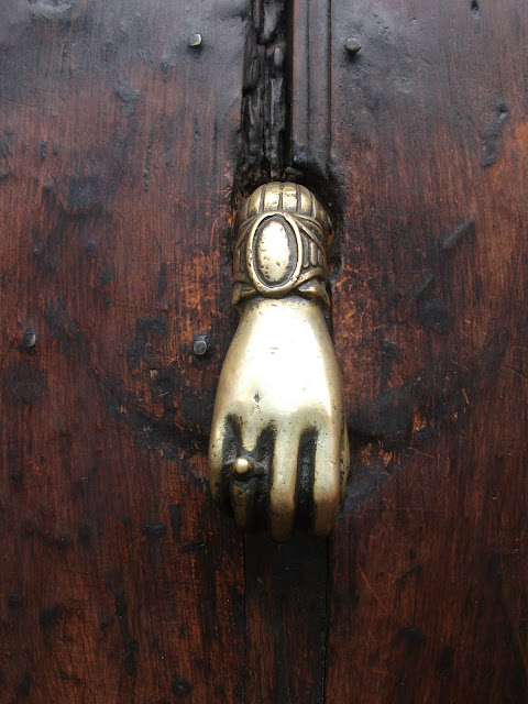 A Latch made out of bronze, shaped as a hand over a wooden door in the Cuernavaca downtown area