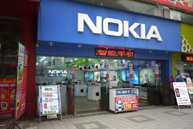 Store with large Nokia sign displaying Apple products