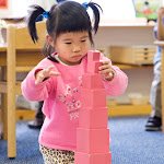 Preschool girl at private Montessori school in Huntington Beach working with pink tower sensorial material.