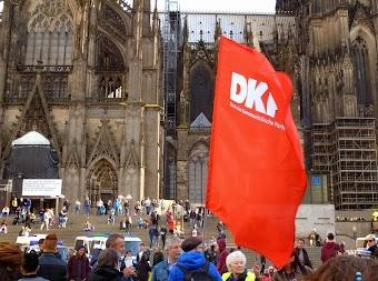 Demonstranten mit DKP-Fahne vor Kölner Dom.