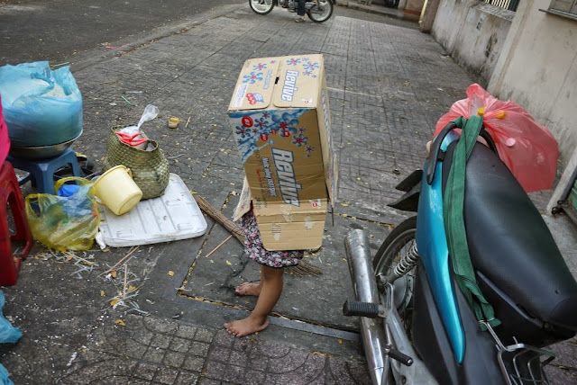 a barefoot girl with a with box over the top of her body playing on a a sidewalk in Ho Chi Minh City, Vietnam