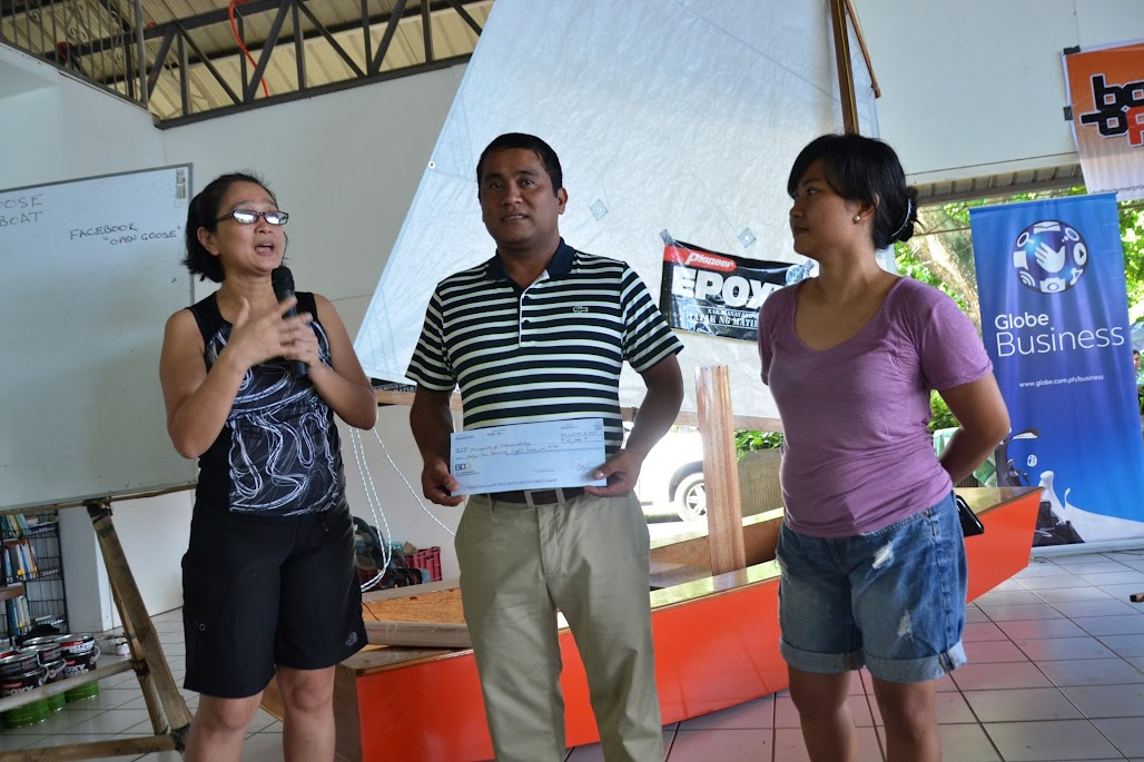 PUSOD TLCC'S ATTY. IPAT JAVIER (R) AND ANNA JAVIER (L) TURN OVER ITS 2014 EARNINGS TO MATAAS NA KAHOY MAYOR JAY ILAGAN DURING THE 1ST DAY OF FAMILY INDEPENDENCE DAY BOAT BUILDING WEEKEND.