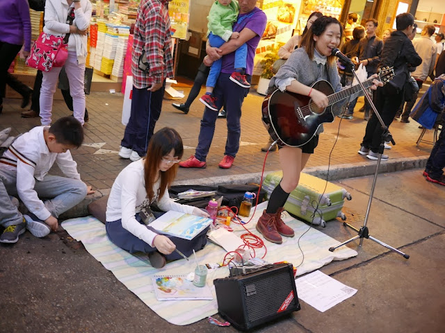 young woman playing guitar and singing at Sai Yeung Choi Street South