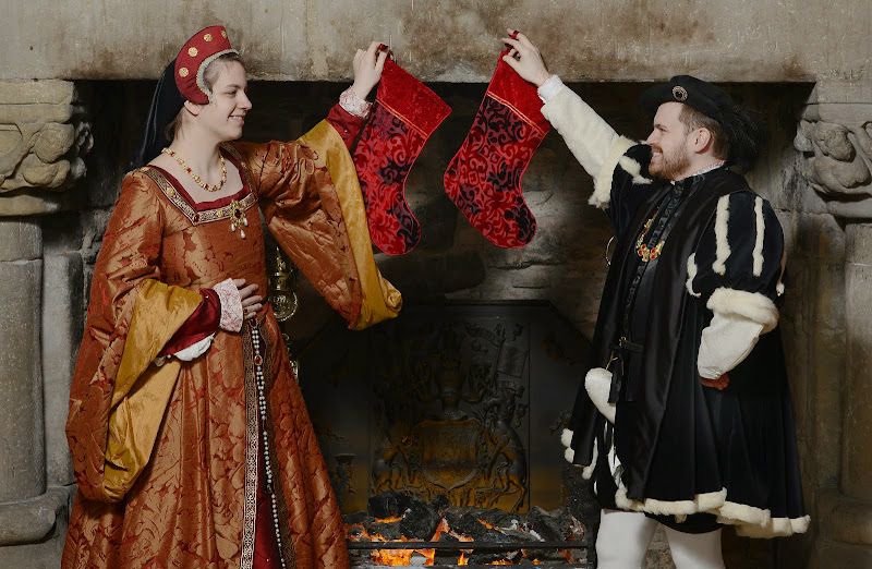 Costumed performers portraying Mairi de Guise and James V hang their stockings in the countdown to Christmas