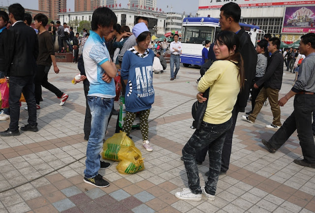 several people standing and talking at Nanmen Square in Yinchuan, Ningxia, China