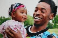 Derek Williams holding his daughter.