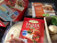 ingredients for making a meal - fajita kit, quorn chunks and fresh onions, mushrooms and peppers.