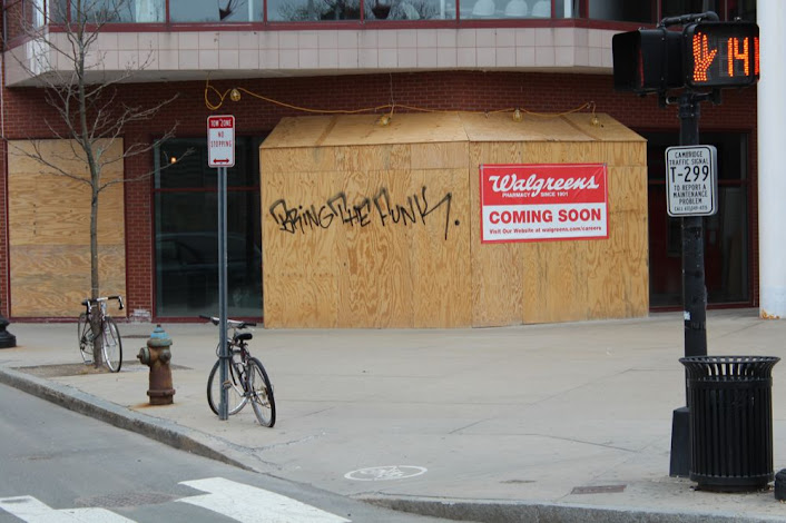 boarded-up store front with graffiti that reads Bring The Funk
