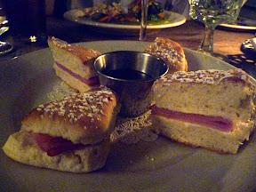 An appetizer of hot smithfield ham biscuits with mascarpone cheese and raspberry puree dip at Gadsby's Tavern