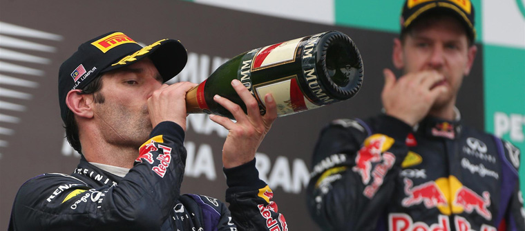 Mark Webber bebe champán bajo la mirada de Sebastian Vettel en el podio de Malasia 2013