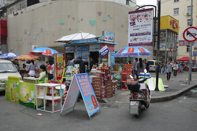 promotion for bottled drinks and other items for sale at a street corner
