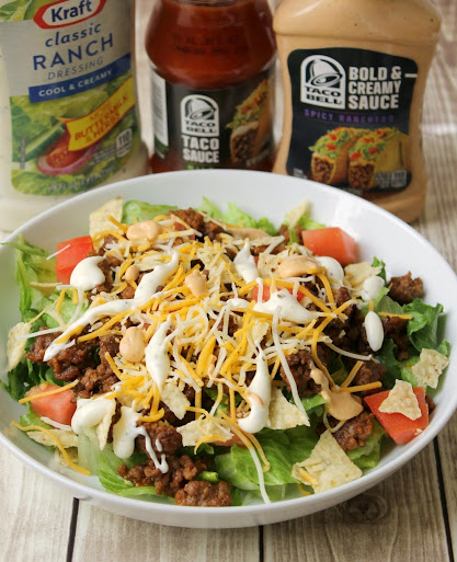 Quick & Easy Taco Salad recipe drizzled with ranch dressing and spicy ranchero sauce