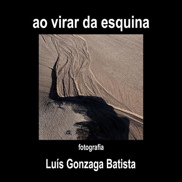 Capa do livro, em fundo preto com letras a branco e quadrado a meio com uma imagem de areia da praia