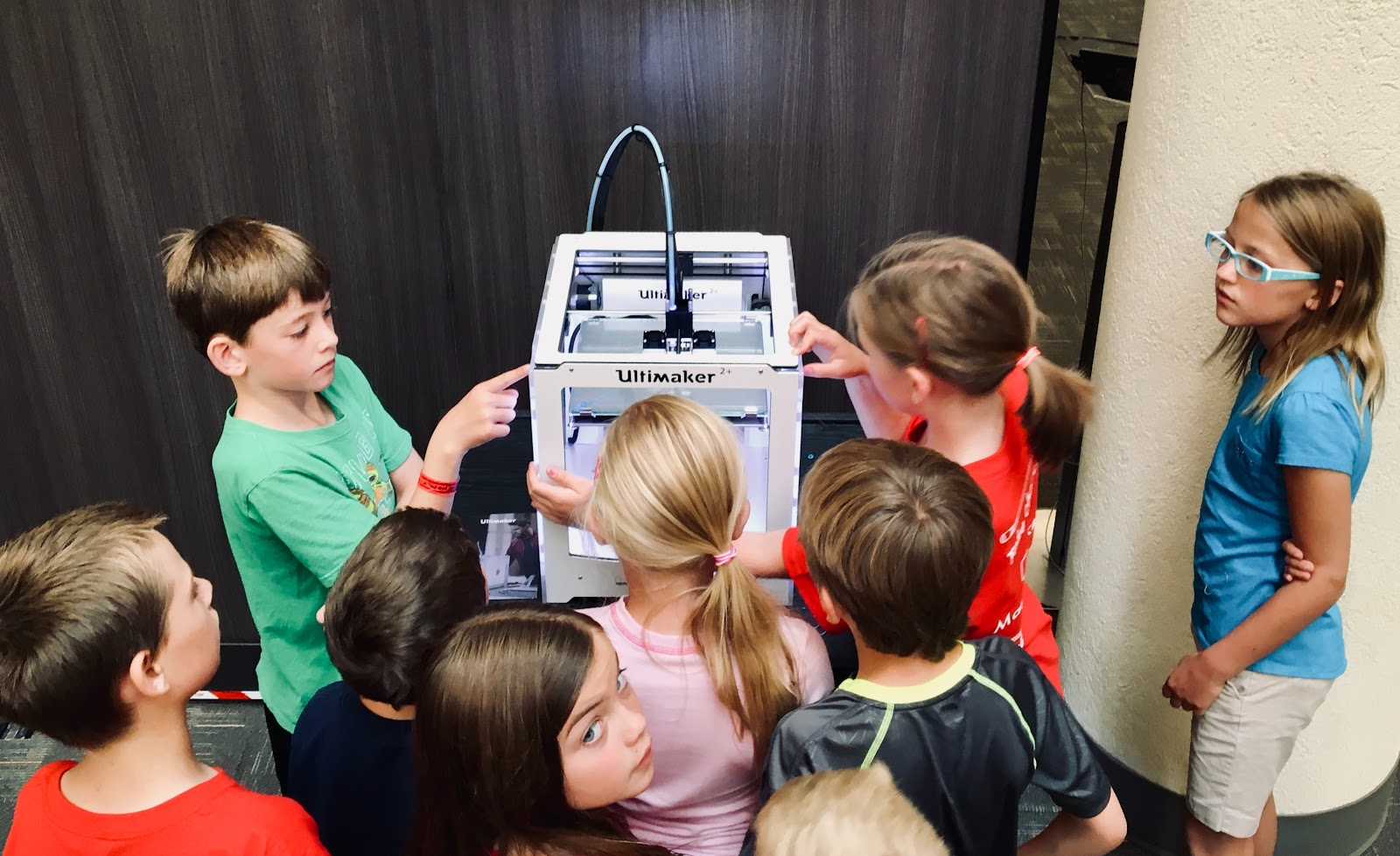 About ten elementary students are gathered around the 3-D printer in their classroom, observing it in action.