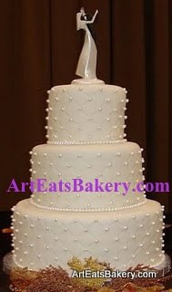 Three tier round white diamond embossed fondant wedding cake with edible pearls and Bride and Groom topper