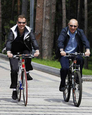 Russian President Dmitry Medvedev (L) and Prime Minister Vladimir Putin (R) cycle in the residence of Gorky outside Moscow on June 11, 2011.
