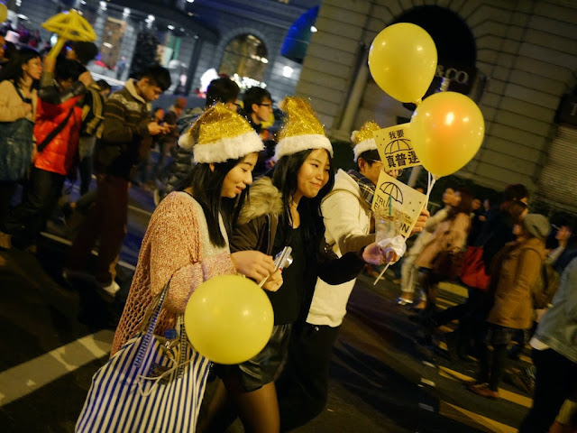 young women wearing yellowish Santa hats and carrying Umbrella Movement materials