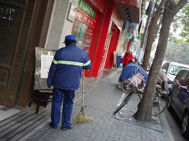 street cleaner with a handmade broom reading a sign in Shanghai