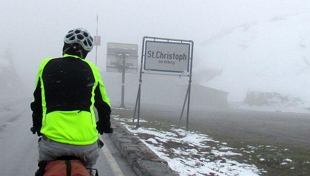 Chris on the Bike in Schnee und Nebel am Ortseingang von St. Christoph am Arlberg, Arlbergpass (1800 m)