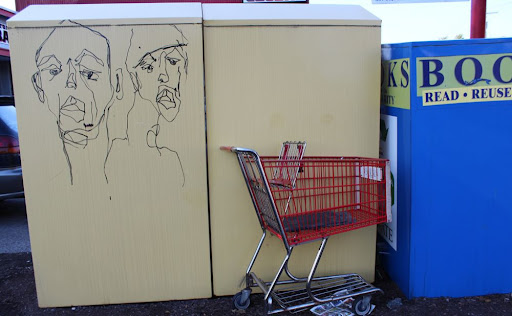 graffiti of two faces on a clothing donation bin; also a shopping cart
