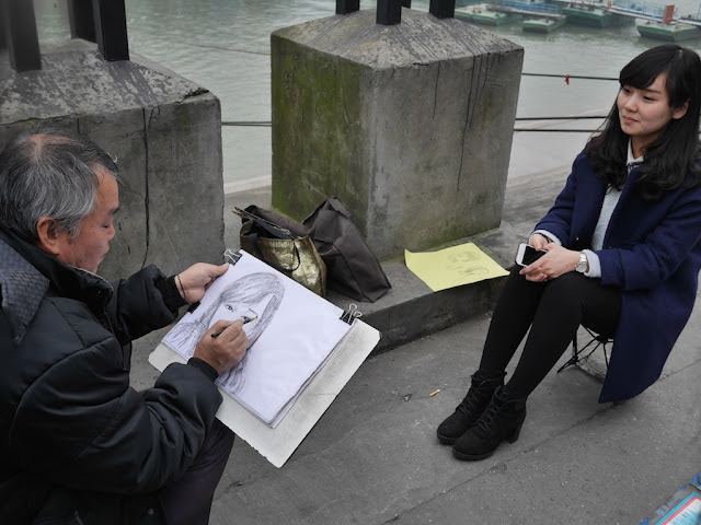 man drawing a younger woman's portait