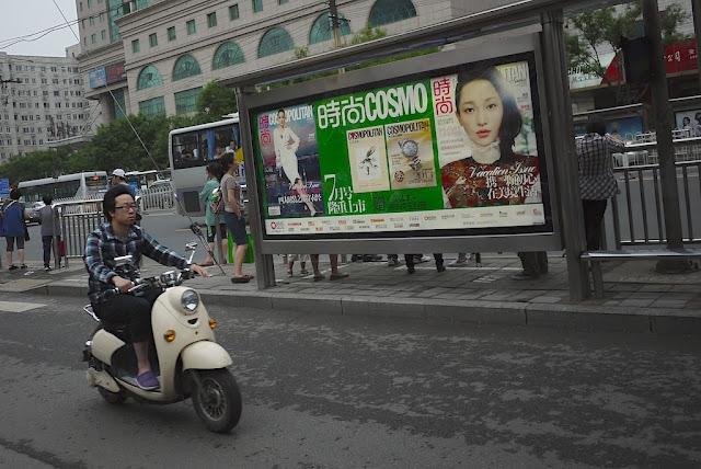 man on motorbike riding by a billboard advertisement for Cosmopolitan magazine