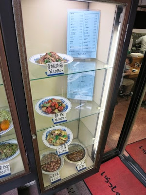 サンプルケースに並んだ青椒肉絲、酢豚などの中華単品特別価格メニュー