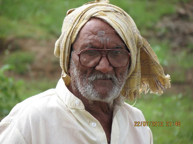 एक स्थानिक आजोबा. वय : अंदाजे ९० / ९५ वर्षे. एकटे काठी टेकत डोक्यावर प्लास्टिक घेऊन उतारावरून आले.
