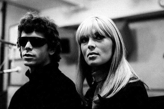 Foto de Lou Reed vestido de cuero y gafas de sol, acompañado por Nico