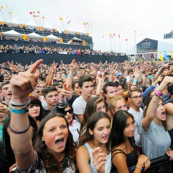 People cheer as they listen to a concert given on the main stage by French rapper Akhenaton of the band IAM (on screen at right) on July 13, 2014 in La Rochelle, during the Francofolies music Festival.