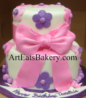 Pink, purple and white fondant two tier custom creative unique lady's or girl's birthday cake design idea with flowers and edible bow