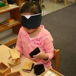 Preschool girl in private Huntington Beach Montessori school working with baric tablets sensorial material.