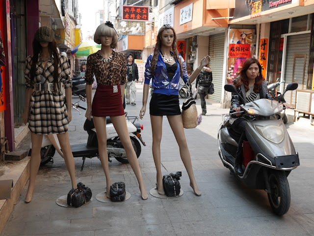 woman riding a motorbike past mannequins in Yangjiang, China