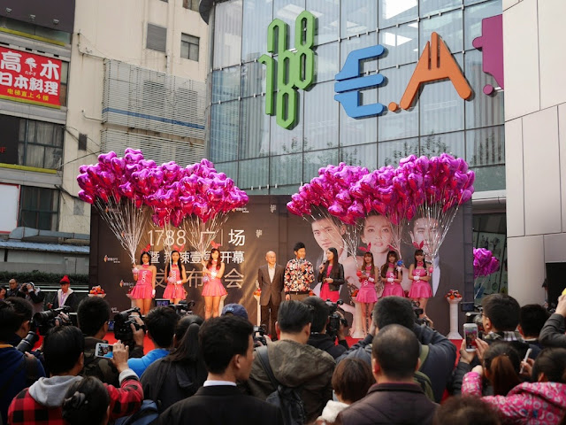 3 people and 6 young women wearing pink dresses and bunny ears while holding large bunches of heart-shaped balloons stand on a stage for an outdoor promotion
