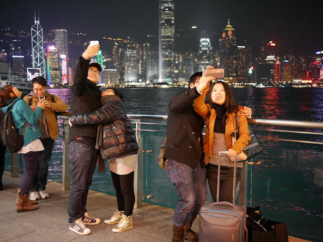 couples taking selfies with the Hong Kong Island skyline in the background