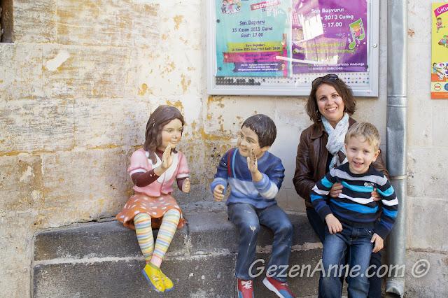 Oyuncak müzesi önünde oynayan çocuk heykelleriyle otururken, Gaziantep