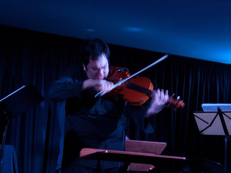 Músico concentrado na sonoridade da viola explorando o arco junto ao afinador