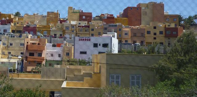 Bunte Häuser hinter einem Zaun, aus dem Auto heraus aufgenommen