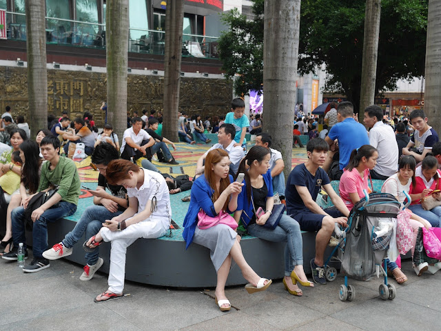 people sitting at a small park in Dongmen