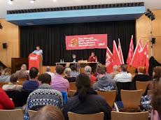 Saal, Teilnehmer, Rednerpult, Bühne mit Fahnen und Transparent: »Der Mensch geht vor Profit – Kapitalismus überwinden! DKP«.