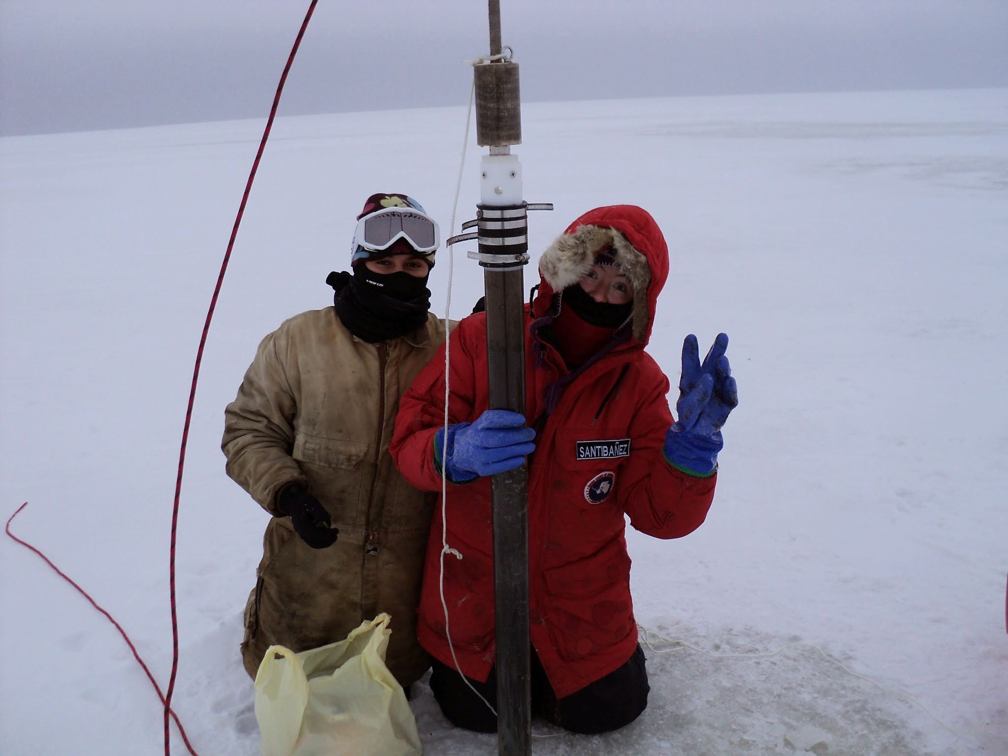 PhD students Paula Matheus-Carnevali (University of Nevada) and Pamela Santibanez (Montana State University) hold a sediment core from one of the lakes near Barrow, AK, October, 2010