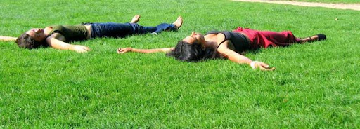 Bruselas Valonia: dos chicas tendidas sobre el césped con los brazos extendidos en el jardín de un parque
