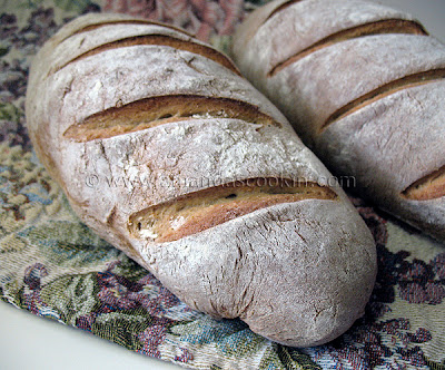 A close up photo of two loaves of rustic rosemary garlic bread.