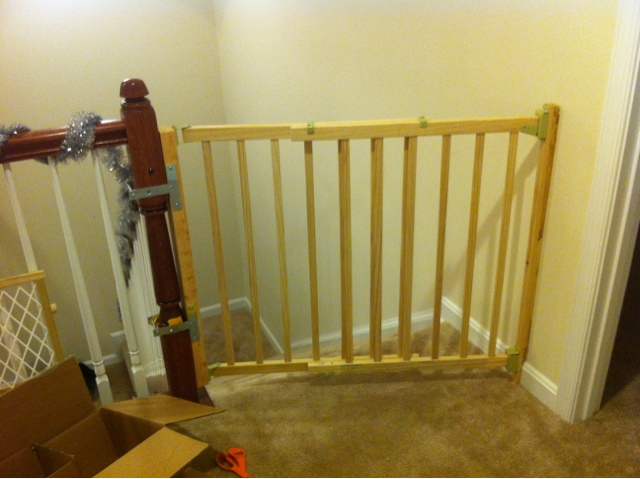 Baby gate for the top of the stairs that is attached to the banister using a diy hack.