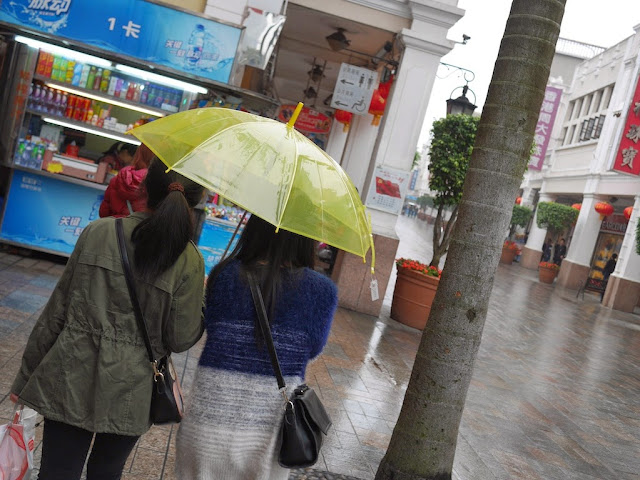 two young women walking under a yellow umbrella