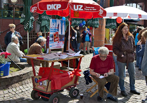 DKP-Stand auf Bollerwagen mit Schirm. Menschen.