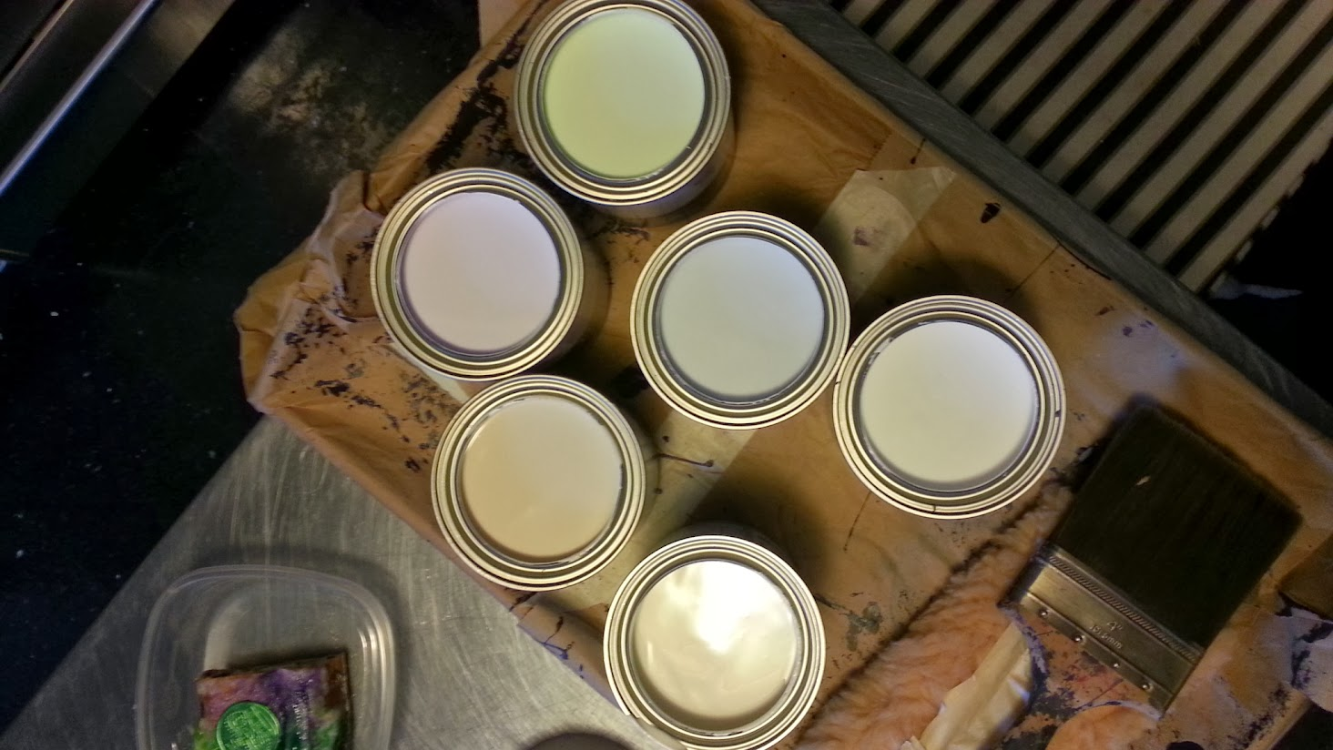 Six quarts of wall paint, lids off, showing six near-white pastel colors