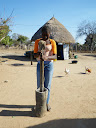 This girl is grinding mealies (maize corn) to make mealie meal.