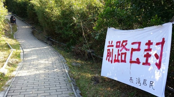 圖:2013 年毅行者比賽期間,大浪西灣村民封閉必經之路,迫使大會臨時改道。Credit: Thomas Fan